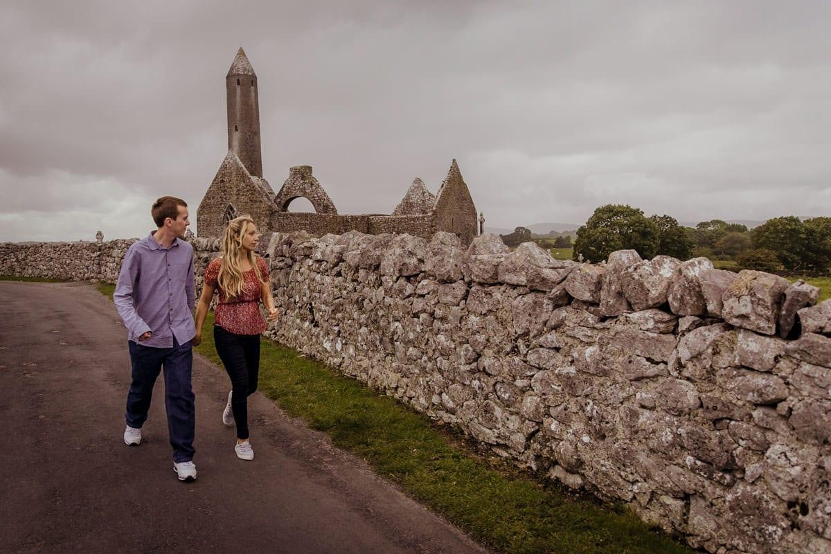couple walking among church ruins west of ireland