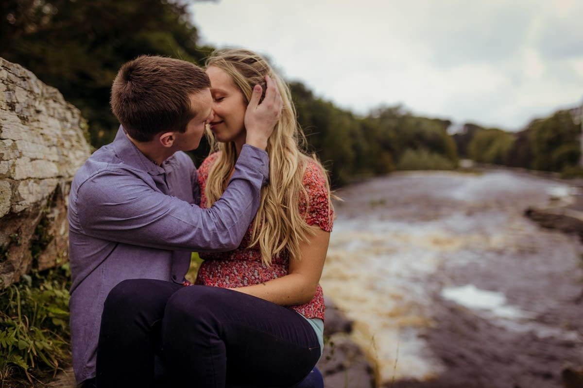 couple cuddling at a waterfall ennistymon falls