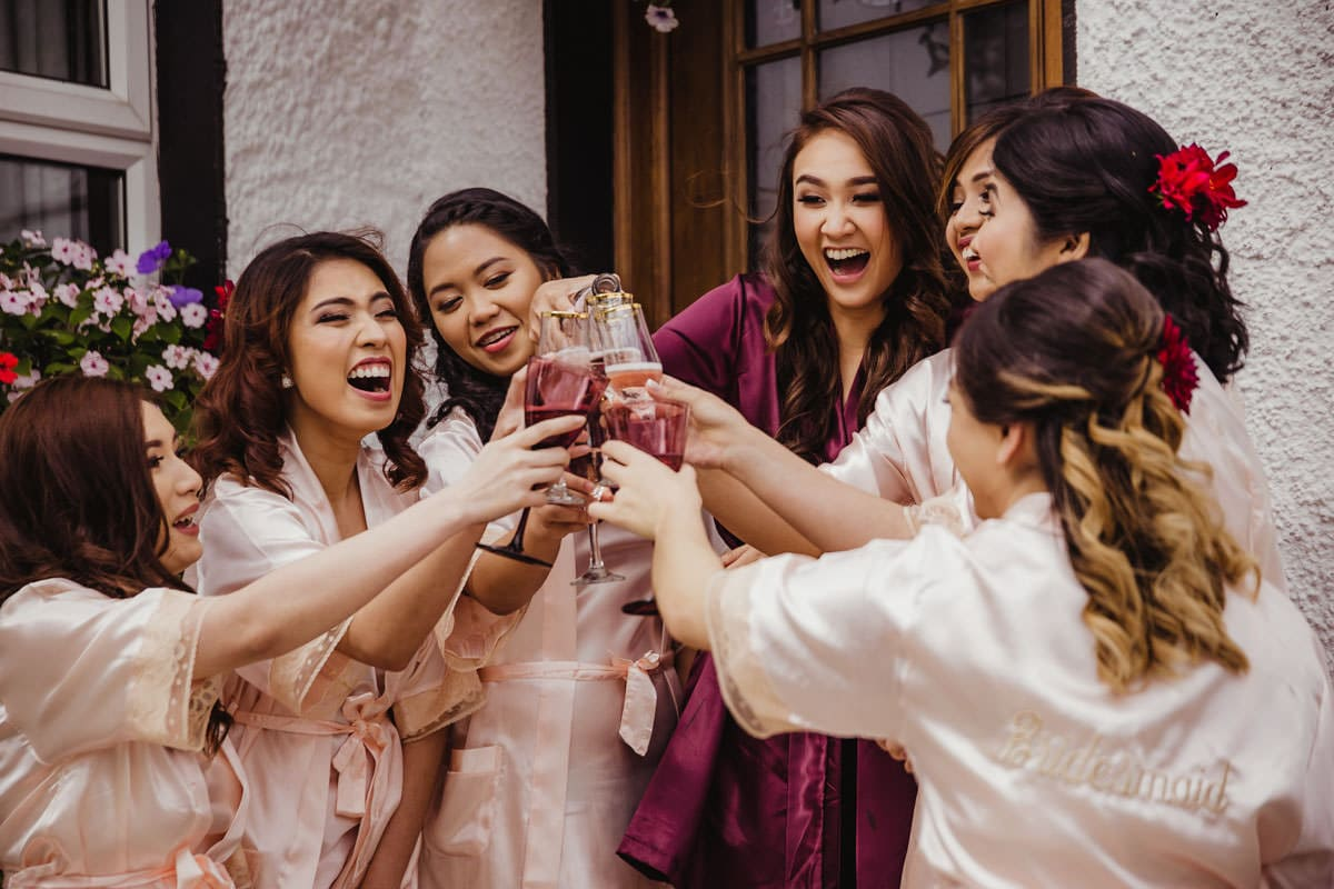 Bride and bridesmaids drinking champagne before wedding ceremony