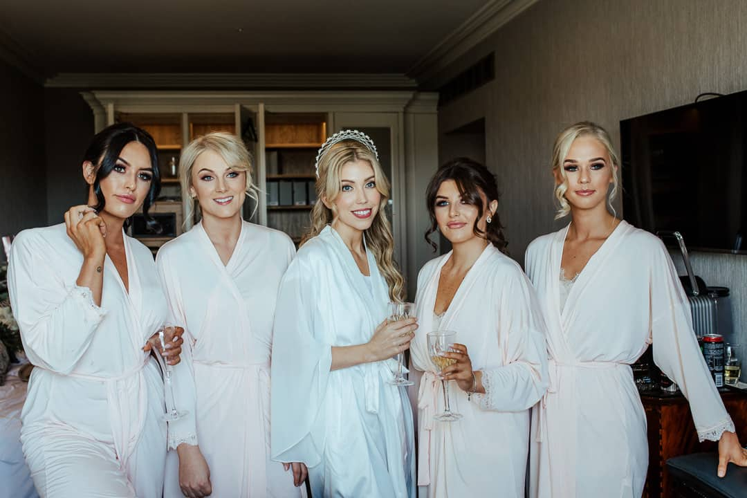 bride and bridesmaids wearing white robes on wedding morning
