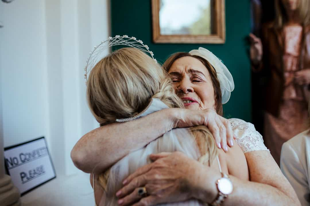 grandmother hugging the bride after wedding ceremony