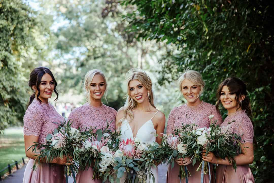 bride and her bridesmaids in pink wedding portraits in st stephen's green dublin
