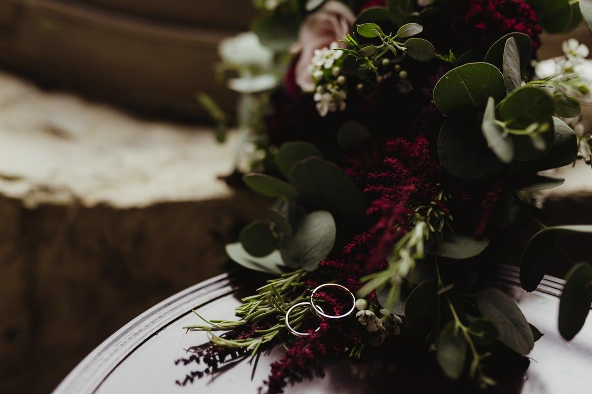 wedding bands on burgundy wedding flowers