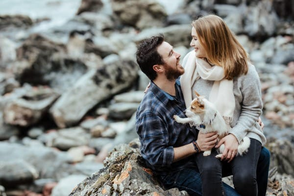couple sitting on a rocky beach with their dog