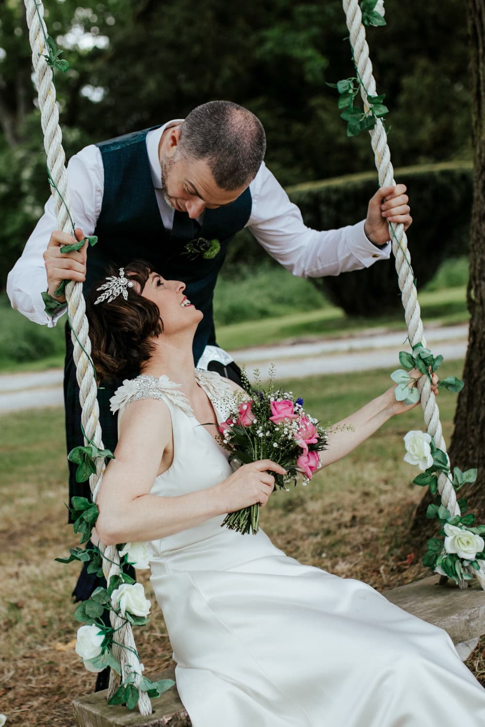 bride and groom having fun on the swing at martinstown house