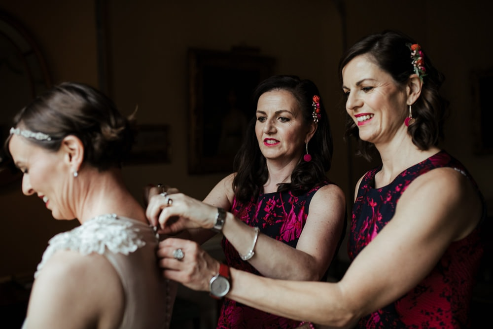 bridesmaids helping bride put on her dress