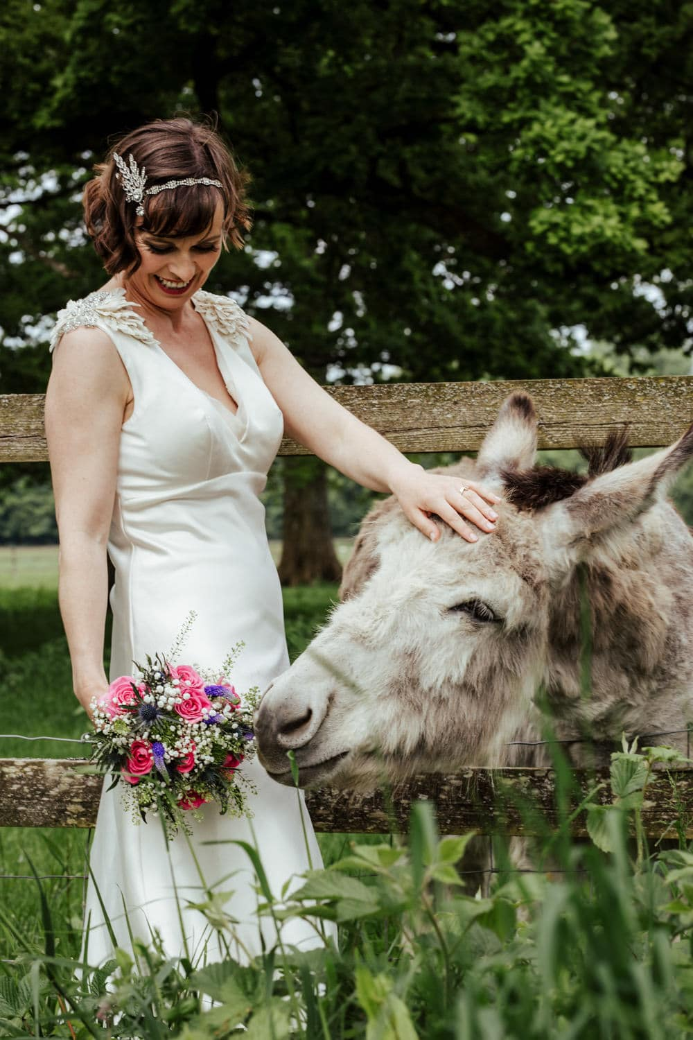 bride feeding wedding flowers to donkey country house wedding venue