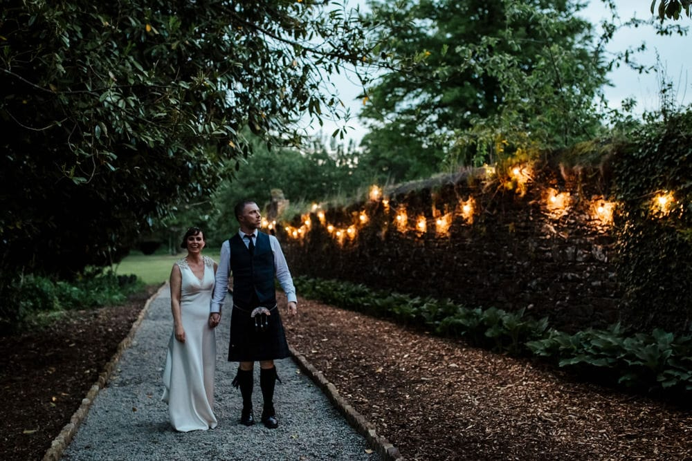 bride and groom taking a walk in evening light at martinstown house