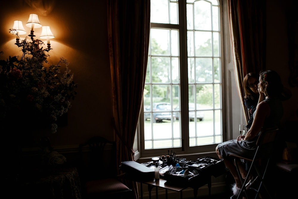 bride getting ready by the large window in martinstown house drawing room exclusive country house weddingvenue