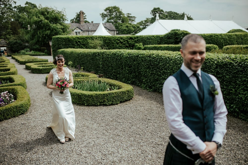 bride walking to meet groom for first look at secret garden in martinstown house kildare ireland