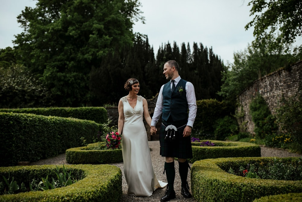 couple walking through secret walled garden at martinstown house wedding venue kildare ireland