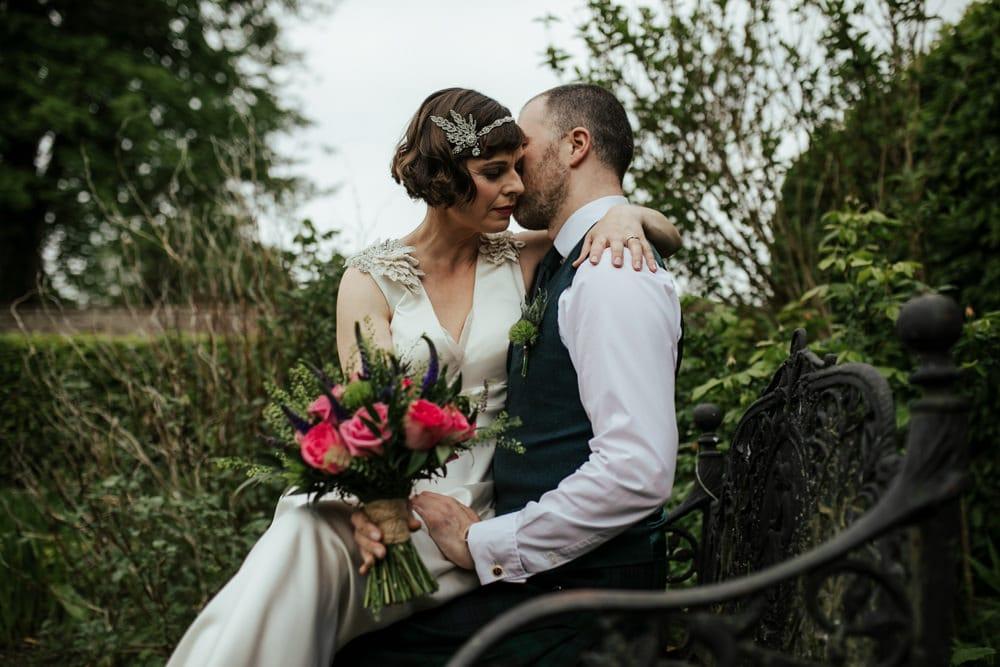 bride sitting on groom's lap cheek to cheek