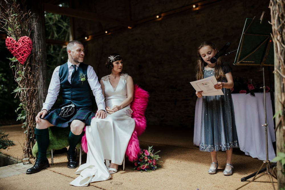 bride and groom listening to a child doing a wedding reading