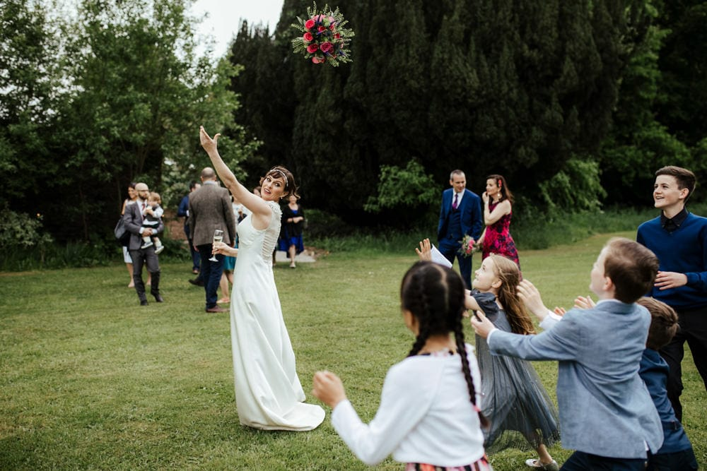 bride throwing her bouquet to group of children