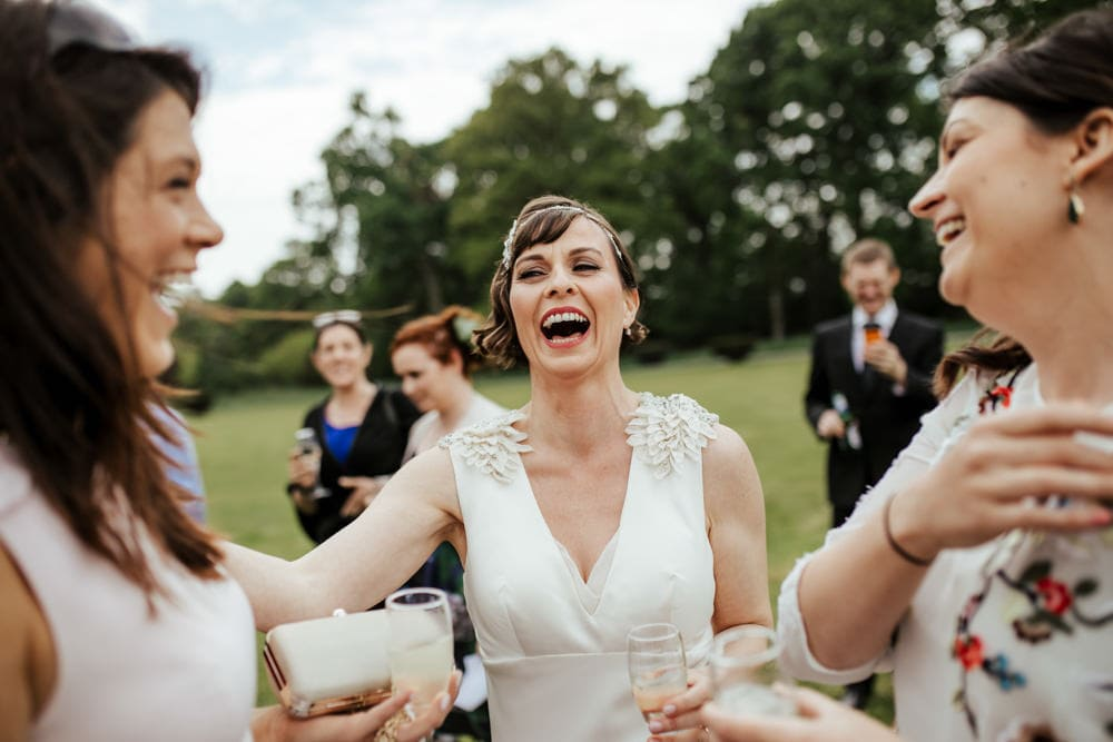 bride laughing with her guests after wedding ceremony