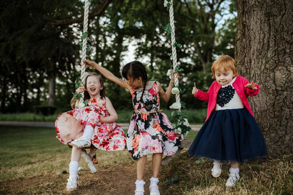 children on a swing at an outdoor wedding