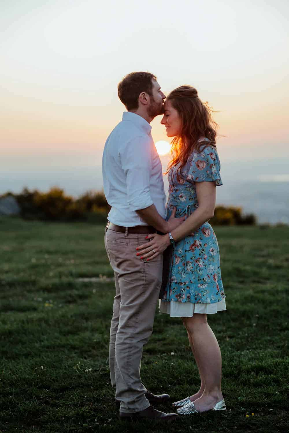 kiss on the forehead romantic couple pose setting sun engagement session