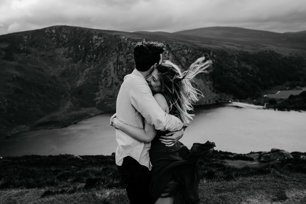windswept engaged couple by Lough Tay