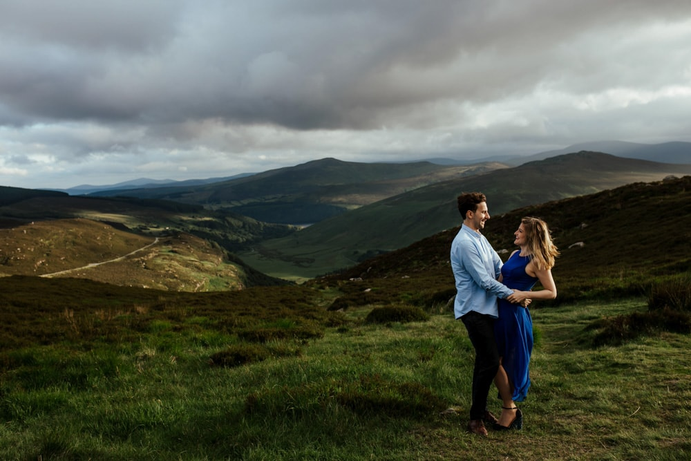 couple holding hands at sunset in irish mountains