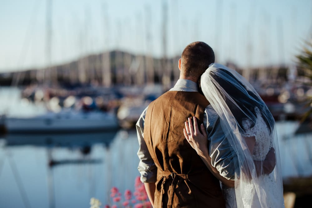 bride and groom in howth harbour looking at the yachts
