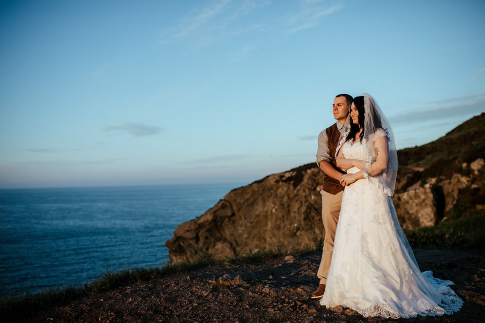 couple at sunset looking out at Irish sea vow renewal ireland
