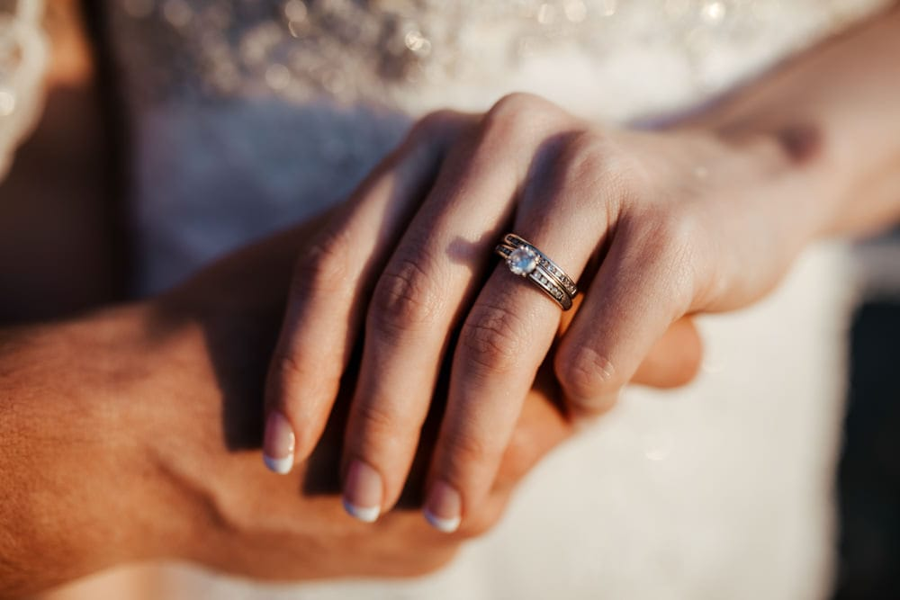 close up of wedding and engagement rings couple holding hands