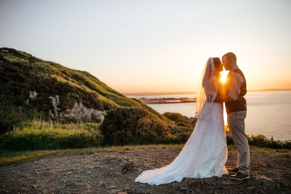 couple kissing in the setting sun on howth cliffs dublin ireland