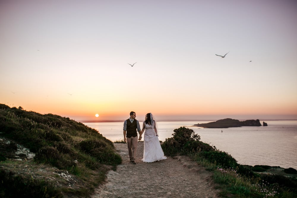 couple holding hands walking in howth at sunset couple photoshoot ireland