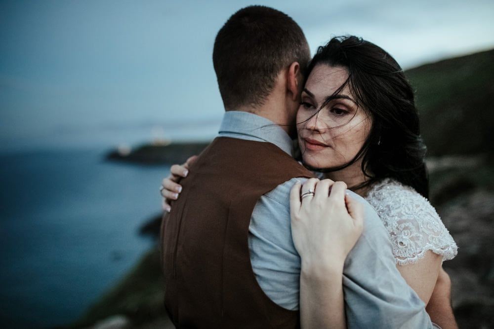 windswept wedding couple on top of howth cliffs after sunset