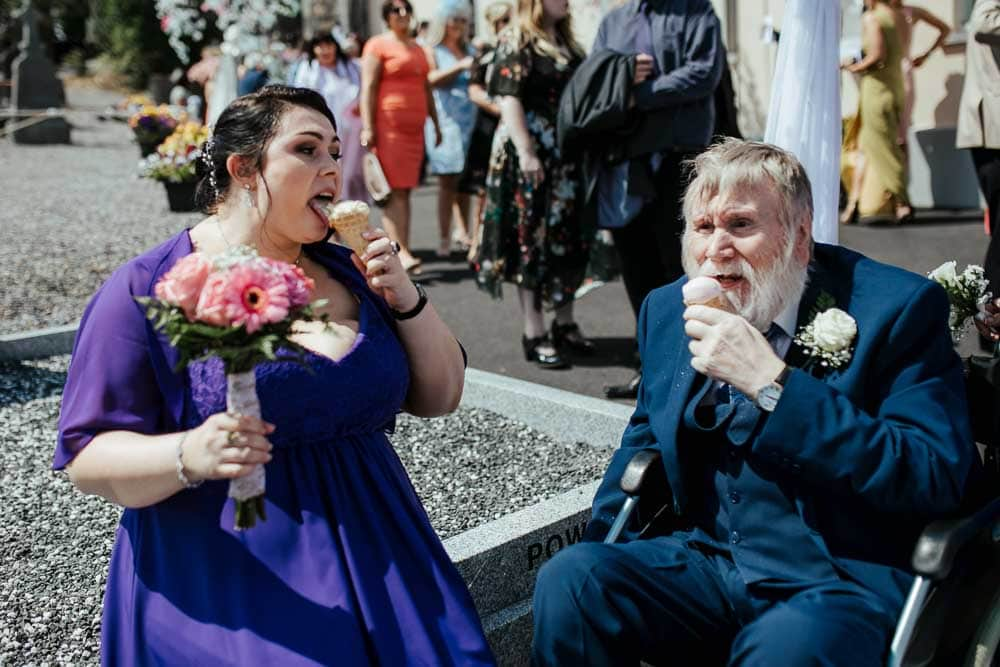bridal party eating ice cream at church yard after wedding ceremony