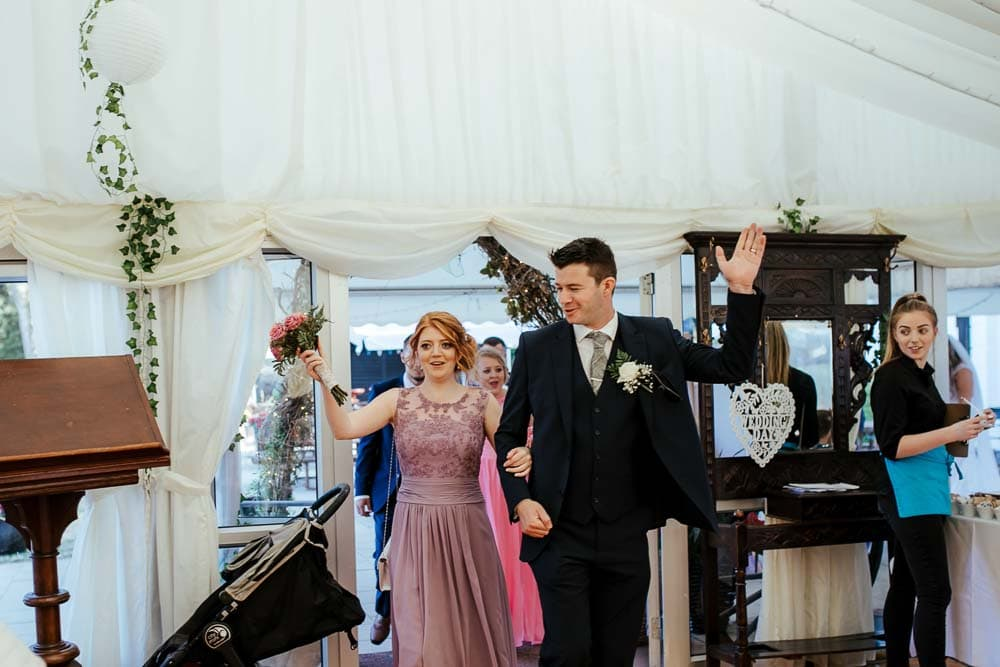 bridesmaid and groomsman entering wedding reception