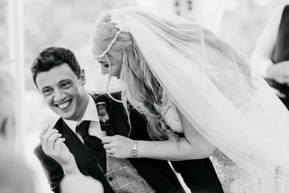 bride and groom laughing during their wedding speeches