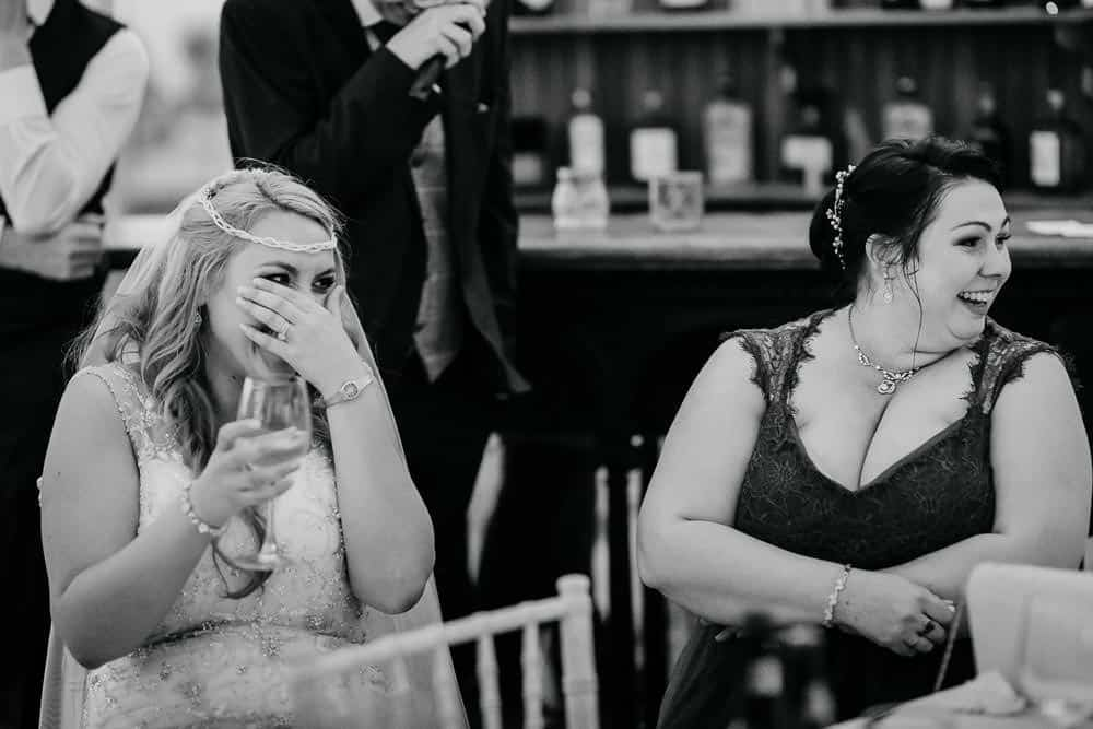 bride and maid of honour laughing at wedding speeches