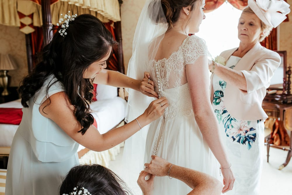 bride getting ready with her mother and bridesmaids