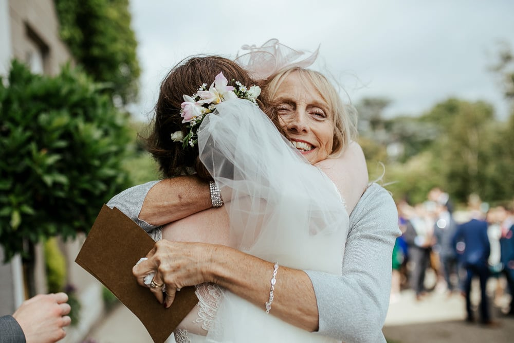 mother of the groom hugs the bride after wedding ceremony