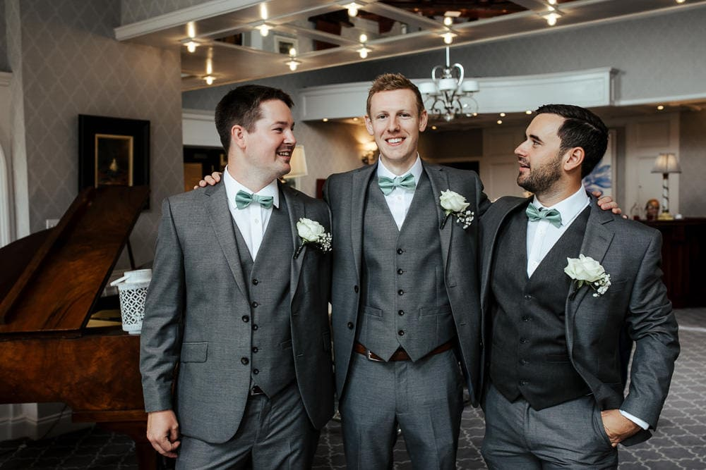 groom and groomsmen in grey suits and mint bow ties