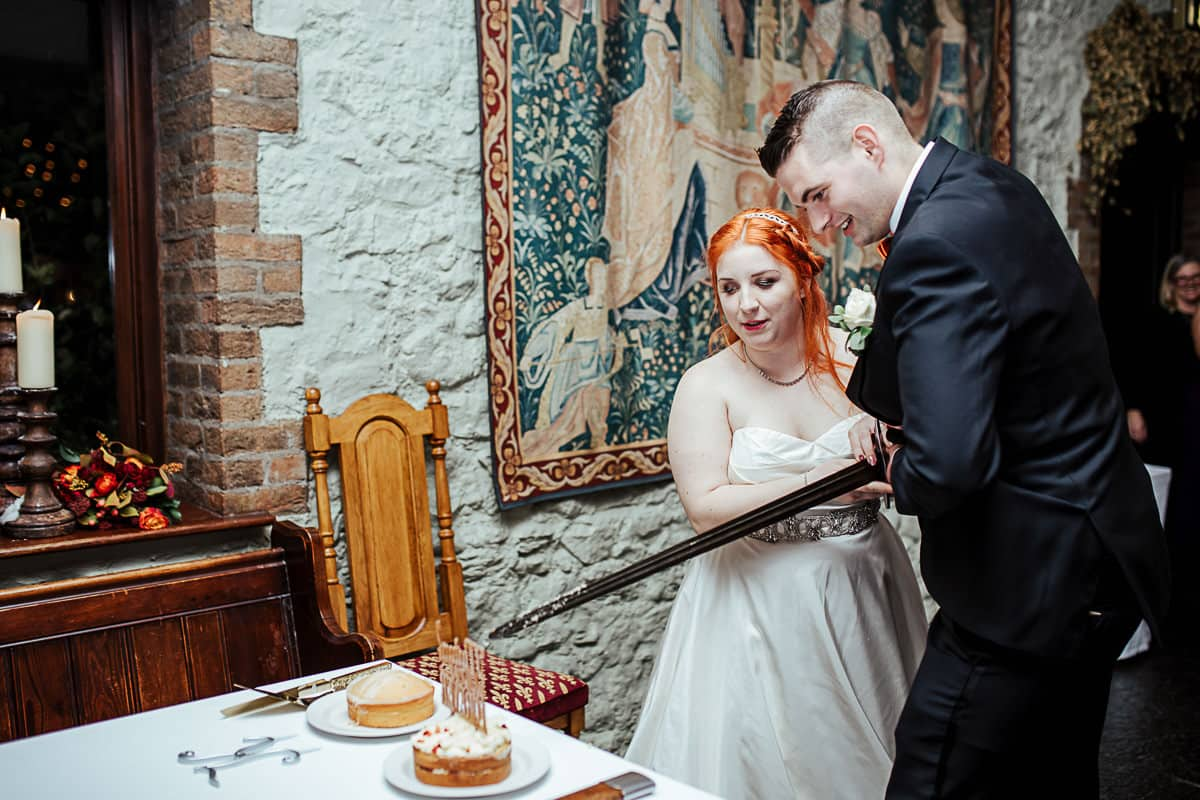 bride and groom cutting wedding cake with a sword barberstown castle wedding