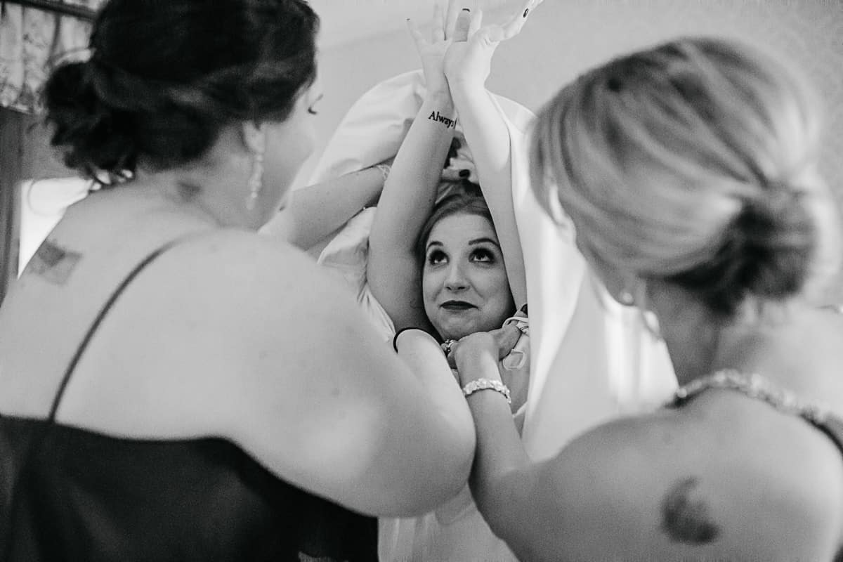 bridesmaids helping bride into her wedding dress