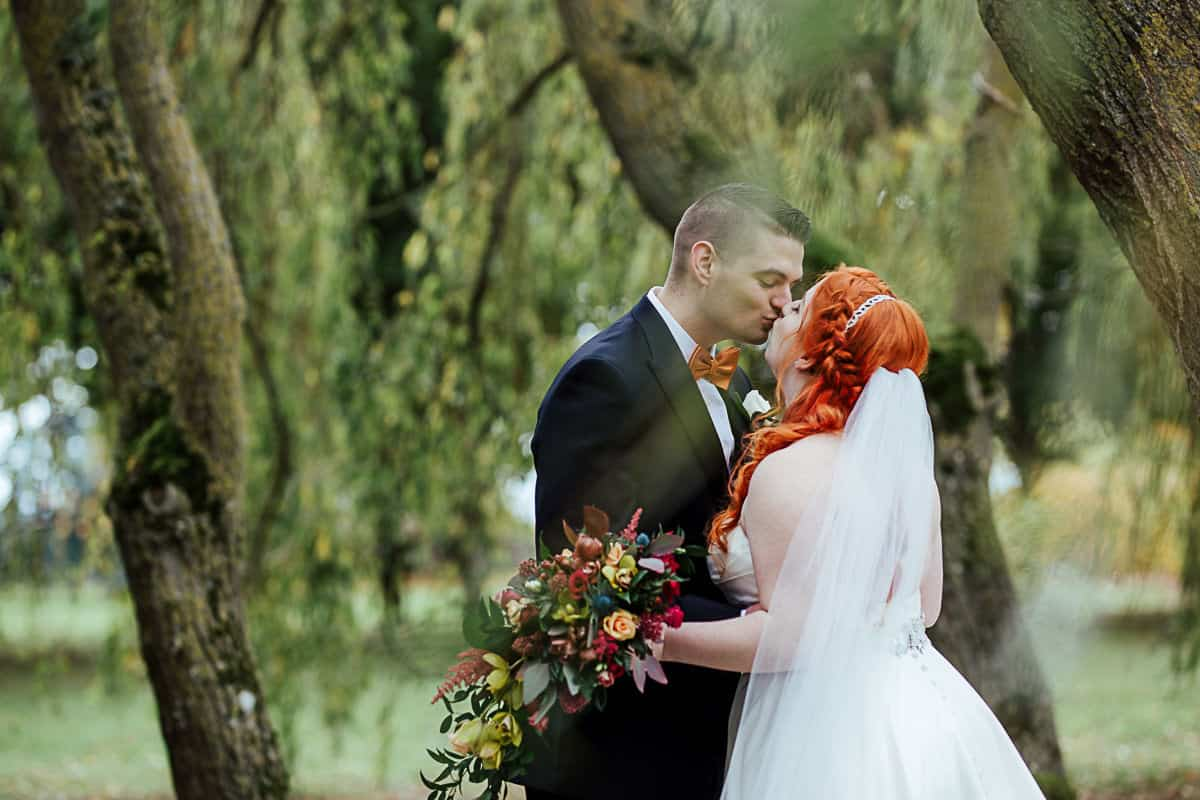 barberstown castle wedding bride and groom kissing under willow tree