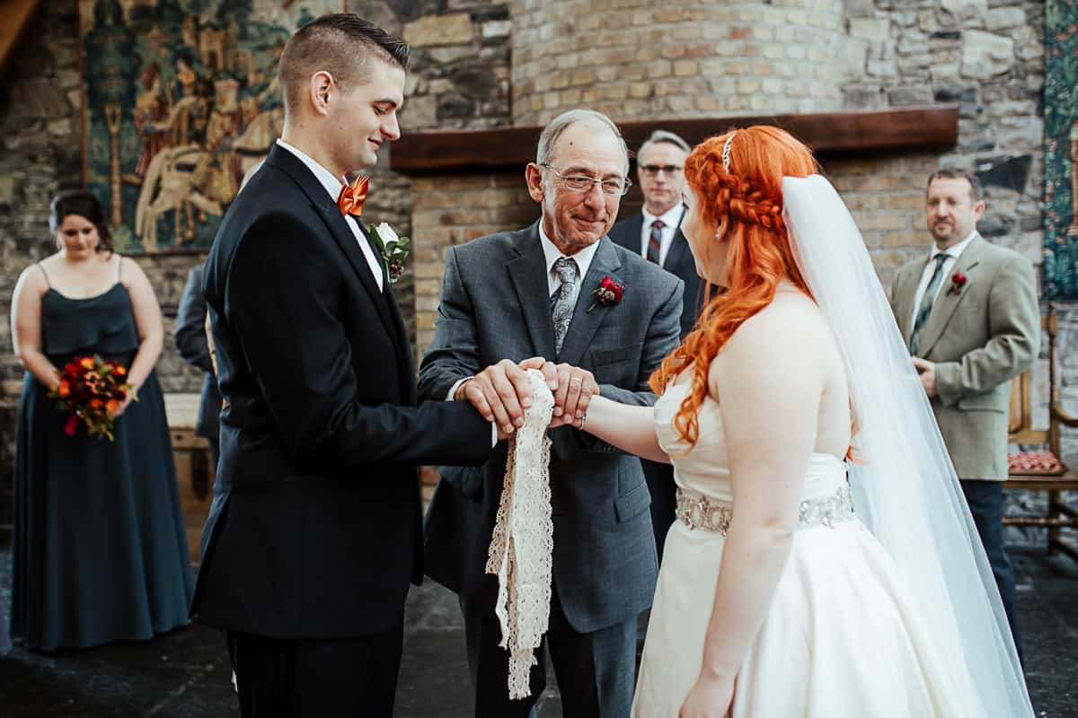 bride's grandfather tying the knot in handfasting wedding ceremony