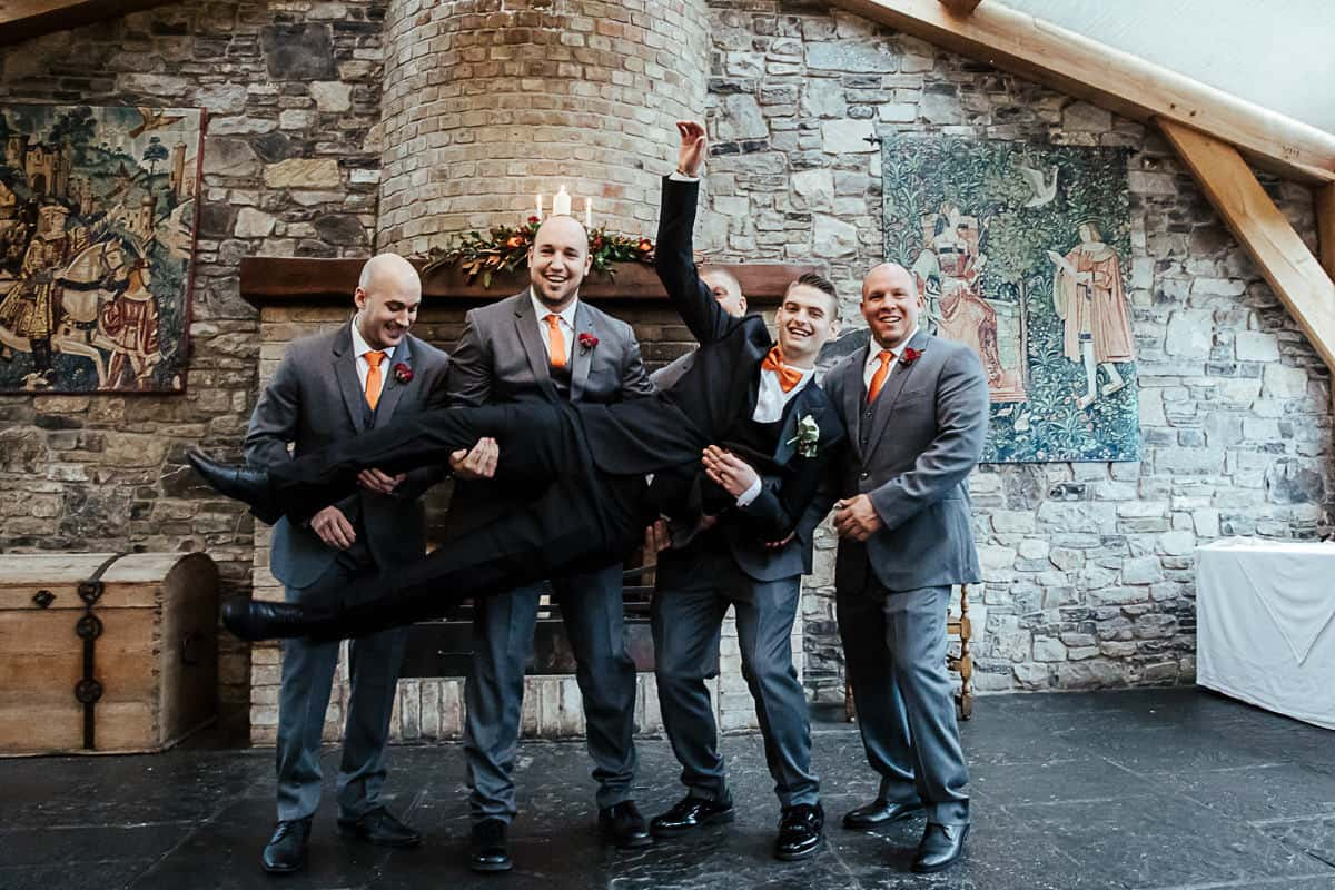 groomsmen in grey suits lifting the groom