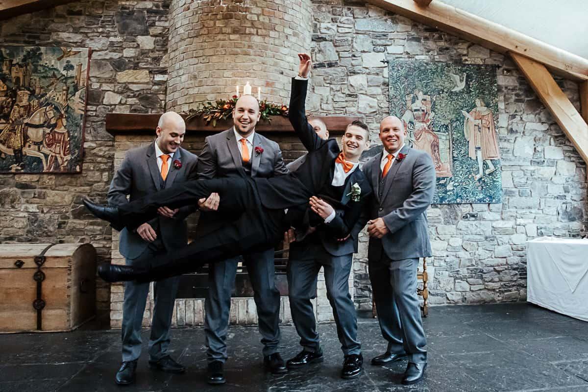 groomsmen in grey suits lifting the groom