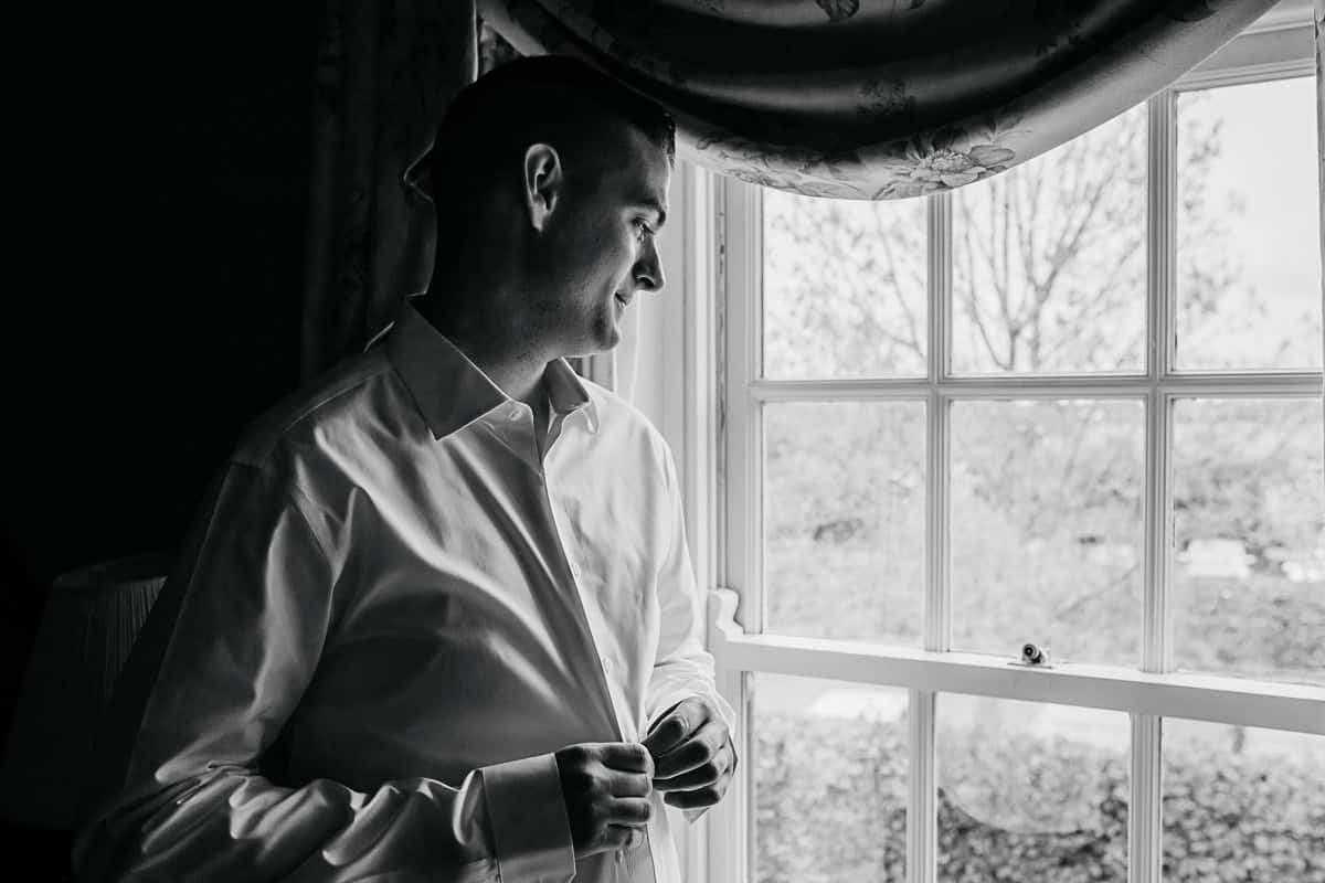 groom getting ready looking out of the window