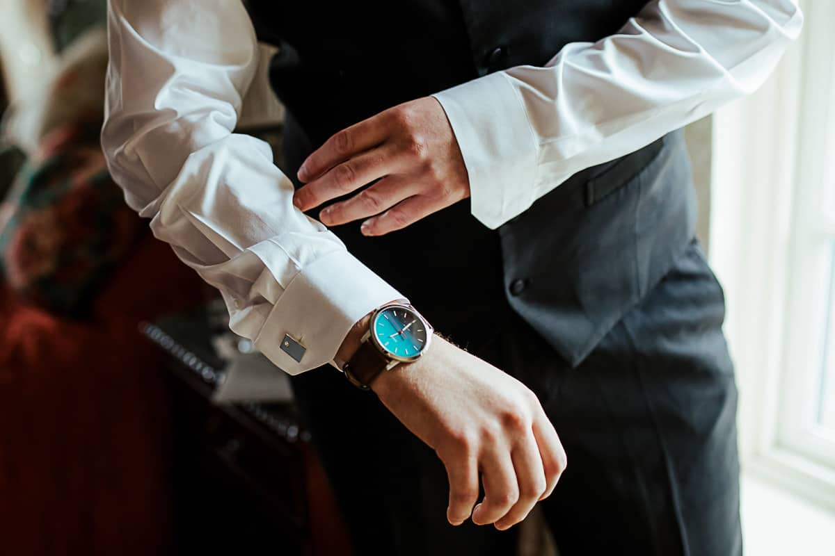 groom getting ready new watch gift from bride