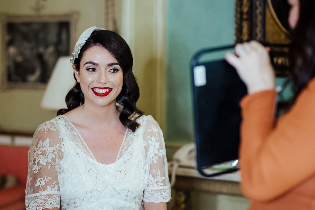 bride seeing herself in the mirror for the first time 50's makeup red lipstick