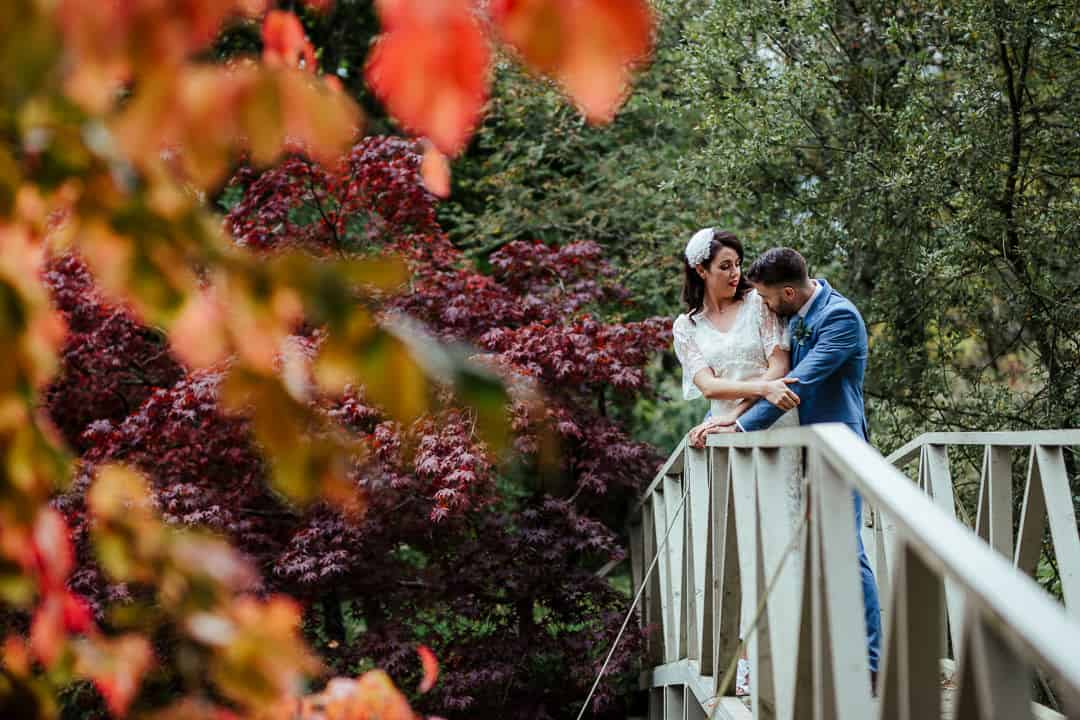 bride and groom on the bridge at marlfield house gardens autumn wedding photographer ireland