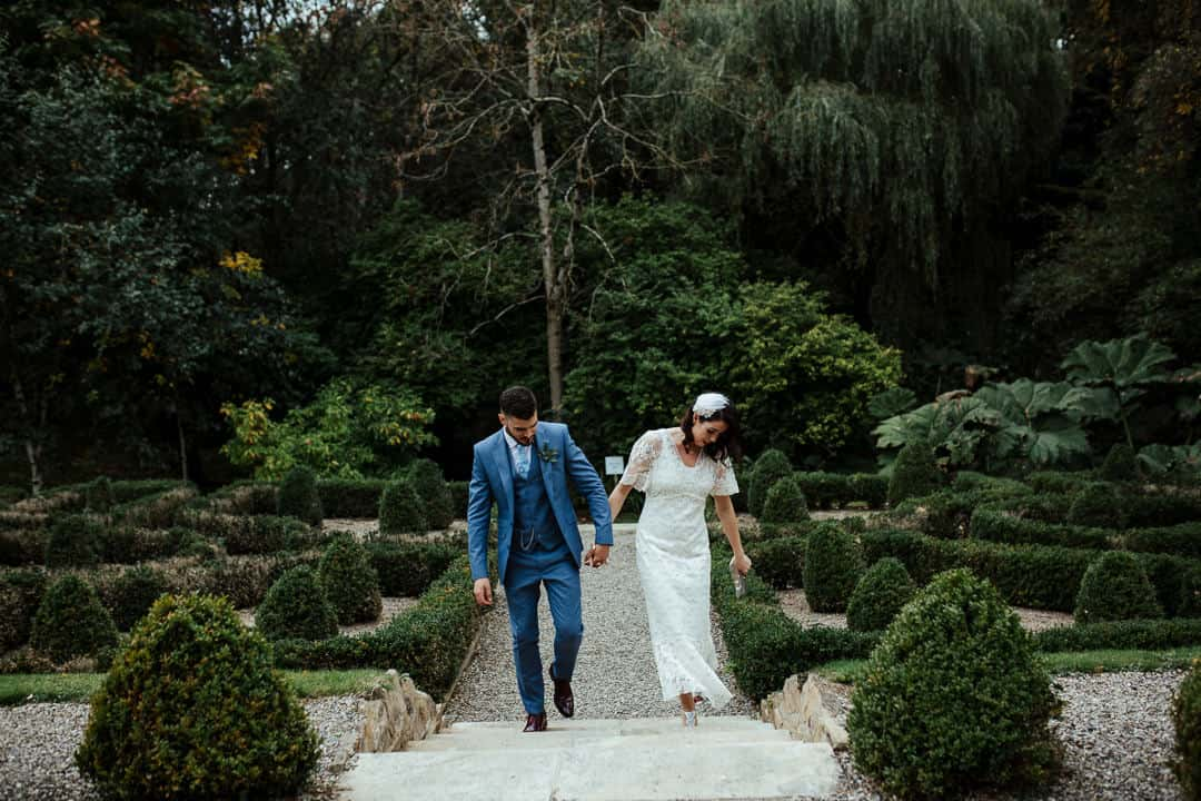 bride and groom walking through the gardens of marlfield house on their wedding day