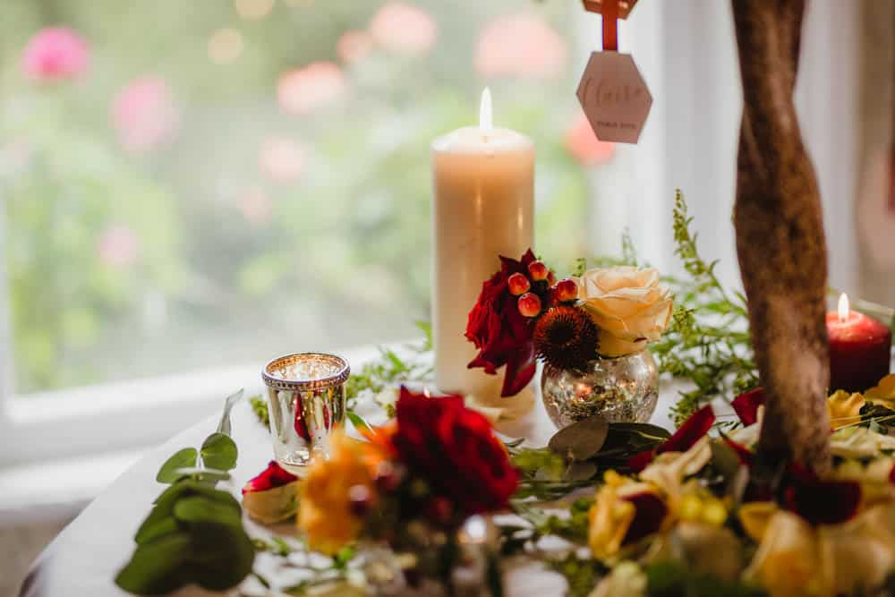table setting for a fall wedding candles and red flowers