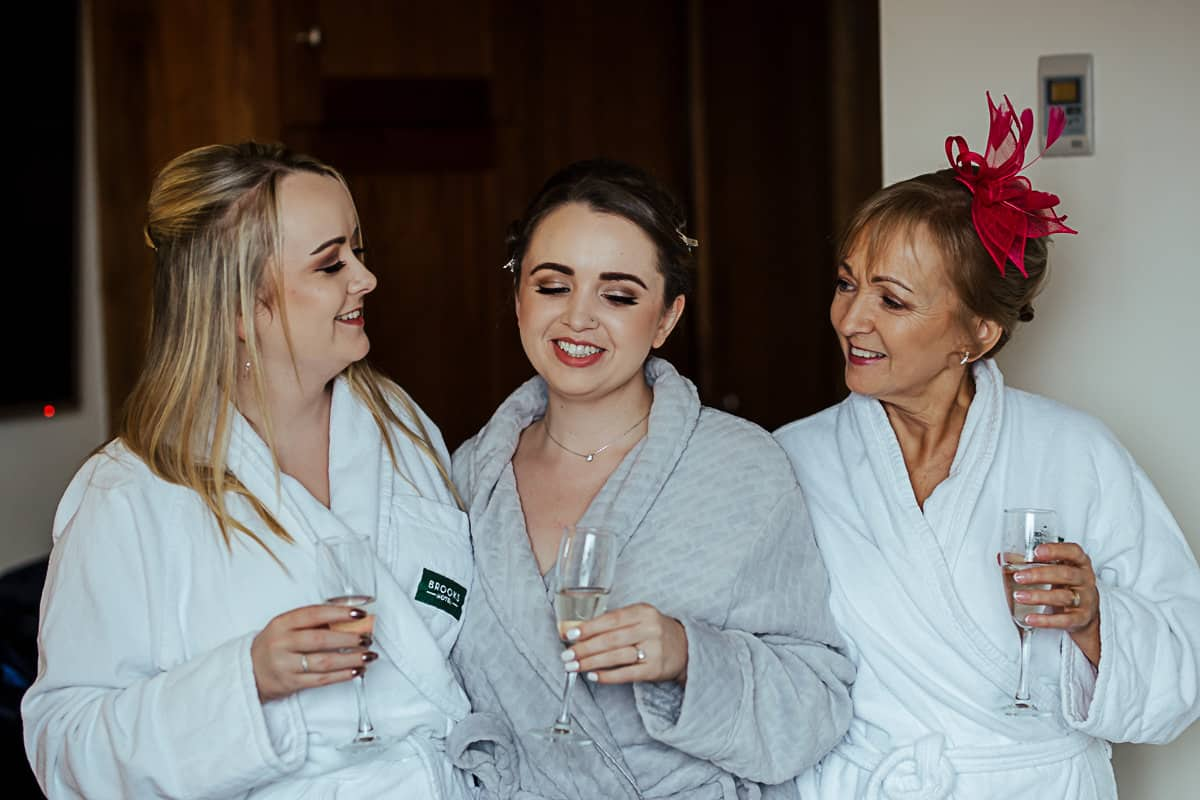 bride drinking prosecco with her sister and mother on her wedding morning