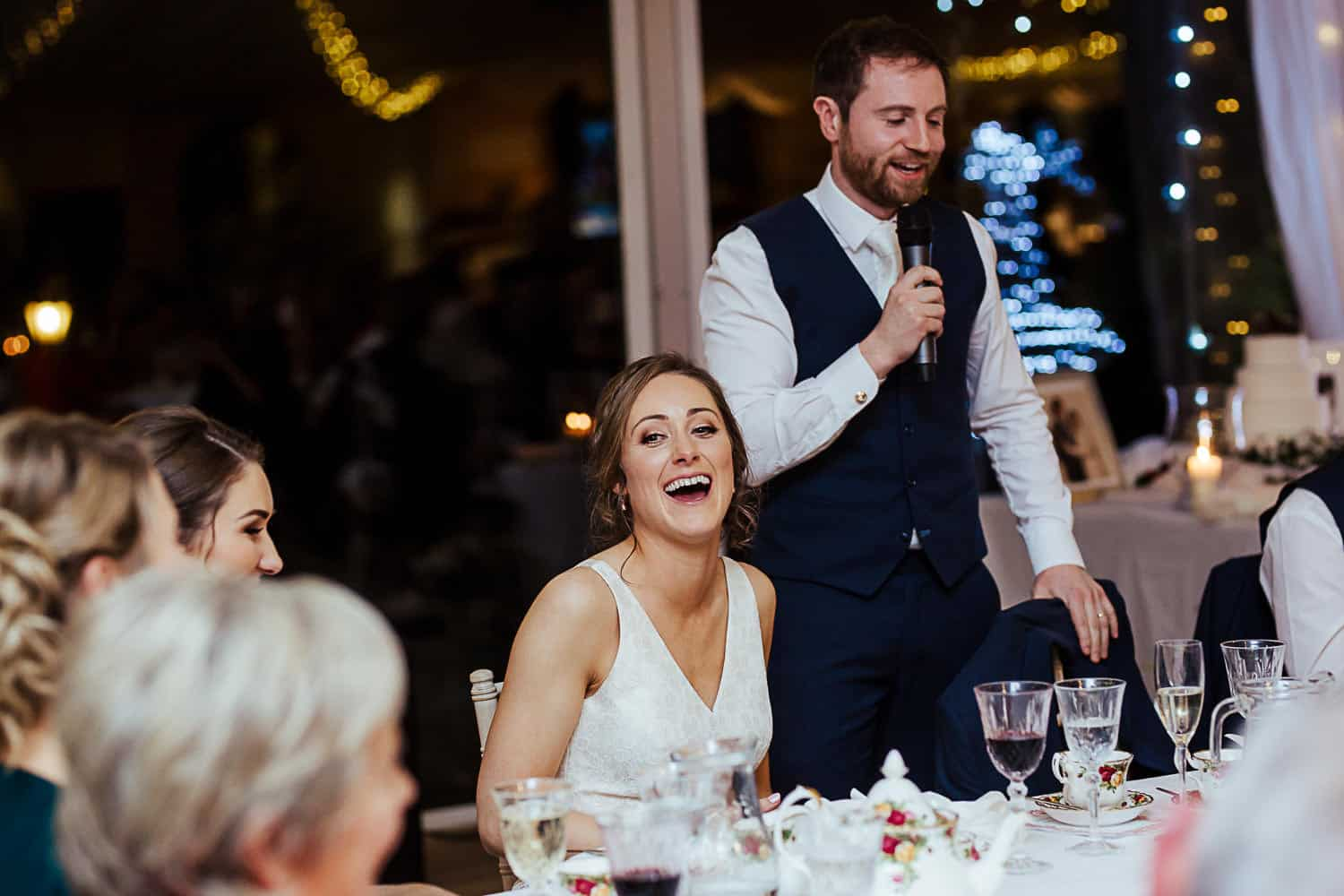 bride laughing during wedding speeches candid wedding photo